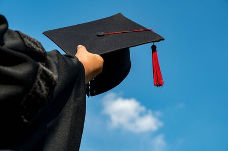 The students holding a shot of graduation cap by their hand in a bright sky during ceremony success graduates at the University, Concept of Successful Education in Hight School,Congratulated Degree