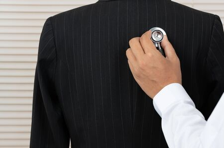 The doctor is using a stethoscope. The doctor has a fever test in the clinic's examination room. Stock Photo