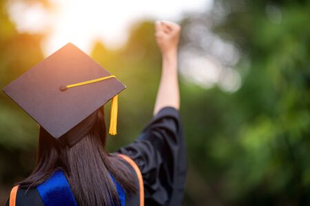 closeup behind a female college graduate wearing a black fringe gown and wearing a black hat with joy, Concept of Successful Education in Hight School,Congratulated Degree