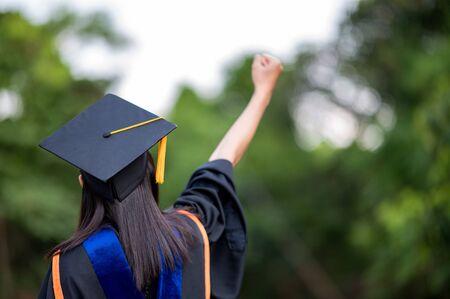 在佩带黑条纹褂子的一位女性大学毕业生背后的特写镜头与喜悦,成功教育的概念在high学校,祝贺的学位