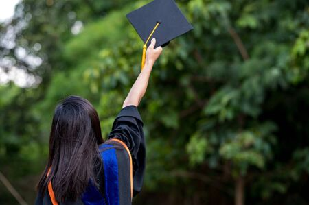 The students holding a shot of graduation cap during ceremony success graduates at the University, Concept of Successful Education in Hight School,Congratulated Degree Stock Photo