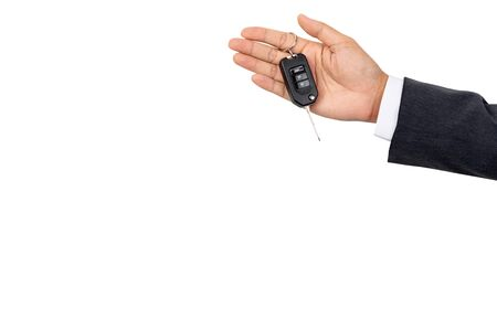 A businessman holding a car key on isolated background and clipping path Stock Photo