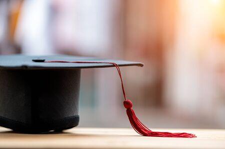 closeup, black graduated hat and red tassels placed on wood and copyspace Zdjęcie Seryjne