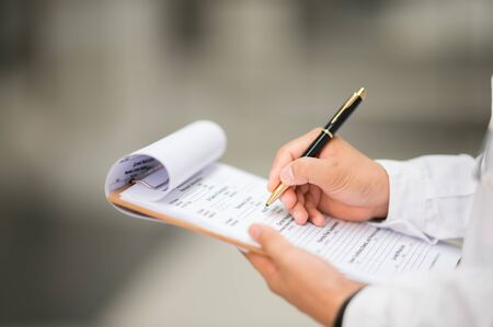 The doctor used a pen to write a diagnosis for the patient. Zdjęcie Seryjne