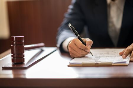 The lawyer is carrying a pen to write a case record in the courtroom