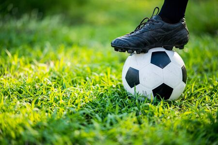 Male soccer football player Use your foot to step on the soccer football during practice on the lawn