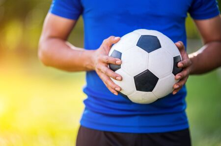 closeup of a soccer football player wearing blue team holding black and white soccer football with blurry bokhe and copy space. Zdjęcie Seryjne