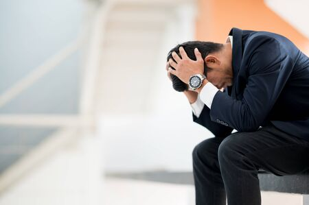 Businessmen use their hands to hold their heads because of economic bankruptcy stress.