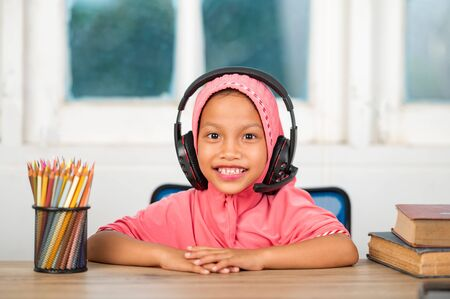 Muslim girls studying online at home To reduce social distance and prevent communicable diseases Archivio Fotografico