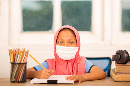 Back to school concept,Muslim girls wearing sanitary masks studying online at home To reduce social distance and prevent communicable diseases Archivio Fotografico
