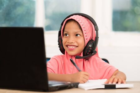 Back to school concept,Muslim girls studying online at home To reduce social distance and prevent communicable diseases