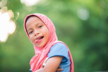 Portrait of a young Muslim girl, covered with red cloth Looking at the camera, smiling, happy and copy space Archivio Fotografico