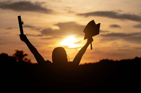 University female graduates Wearing a black robe, wearing a black hat, looking at the sunset