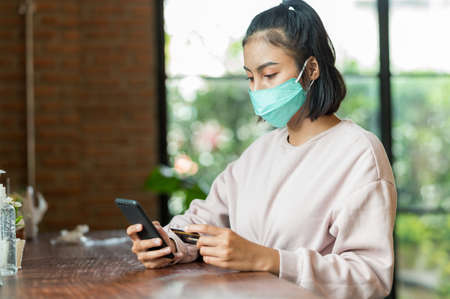 Woman wearing surgical mask in cafe shopping online with Mobile Phone