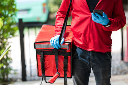 delivery man red cloth Searching for customer address by mobile phone 版權商用圖片