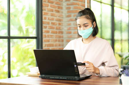 Woman wearing surgical mask in cafe shopping online with laptop