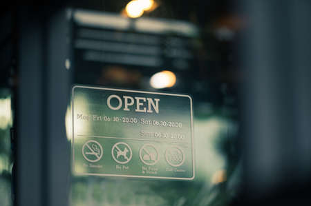 Open sign hanging on window glass at SME Small business
