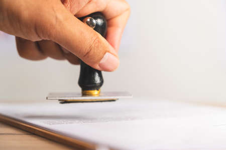 Close-up Of rubber stamp for Approved document At Desk