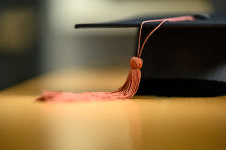 Close up hand of Graduate holding Graduation hat on the green chalkboard background,Education Success Concept 免版税图像