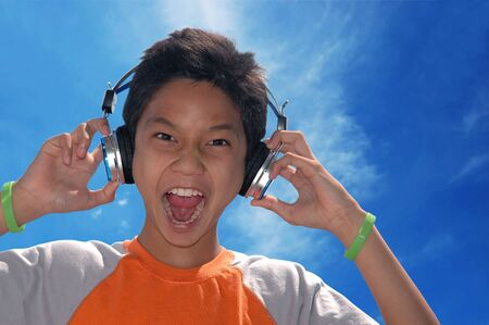 A boy singing while listening to music on his headphone