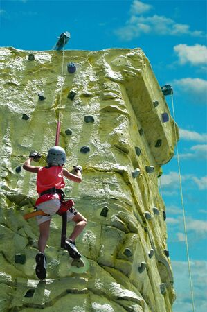 A young boy climbing to his goal on a rock wall