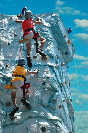 A team (two kids) climbing the top of a rock wall Stock Photo