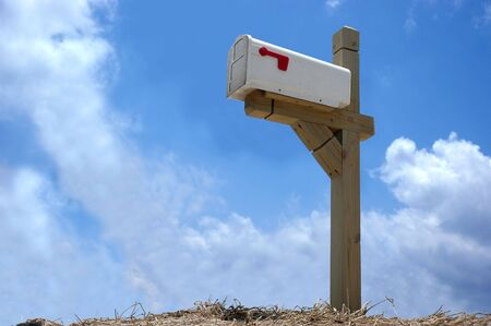 retrieve: A mailbox mounted on wood stand in clear blue sky background