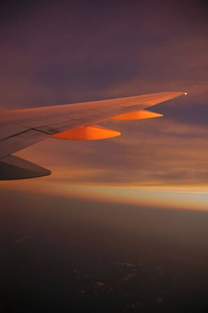 A wing of an airplane in flight at sunset Stock Photo