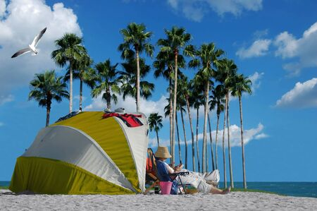 A person relaxing beside a tent on the beach
