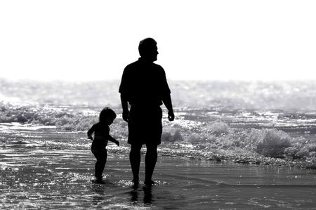 A father and child strolling on the beach. Stock Photo