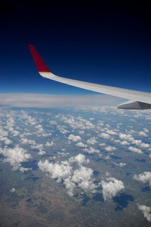 An airplane's wing high above the clouds Stock Photo