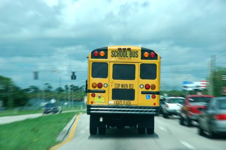 A moving school bus along traffic Stock Photo