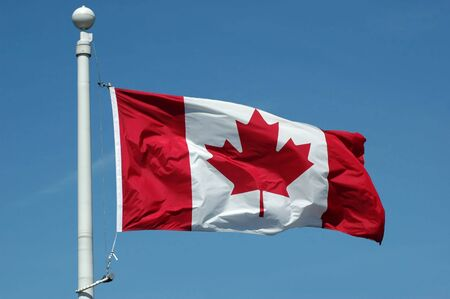 Canadian flag in blue sky background Stock Photo
