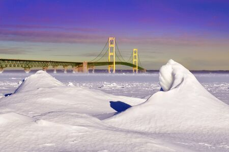 Winter landscape near sunset of the Mackinac Bridge and the frozen Straits of Mackinac, Michigan's Upper and Lower Peninsulas, USA Stock Photo