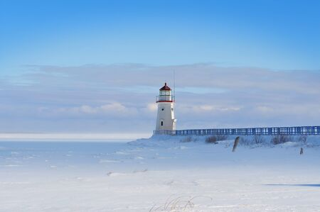 Lighthouse in a calm and desolate winter landscape Stock Photo