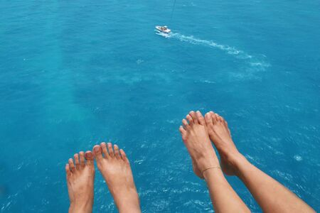 View of feet of couple parasailing with the speed boat in the sea background