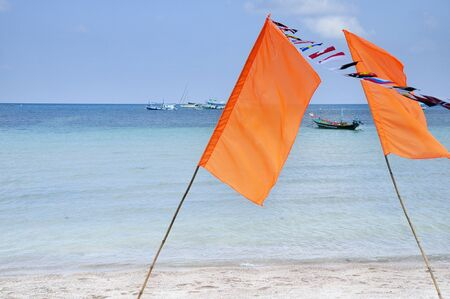 flags against blue sky, sea and boat photo