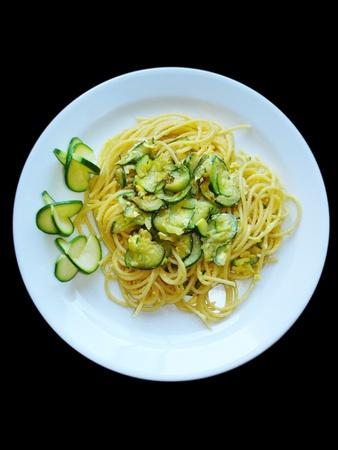 Deliciosos espaguetis italianos con calabac�n. El fondo negro para las industrias de restaurantes, men� y la comida. Pasta para la dieta mediterr�nea. Vista desde arriba.