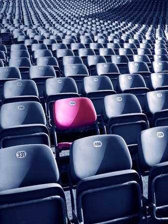 Uniqueness concept represented by red-pink colored stadium seat. There photo