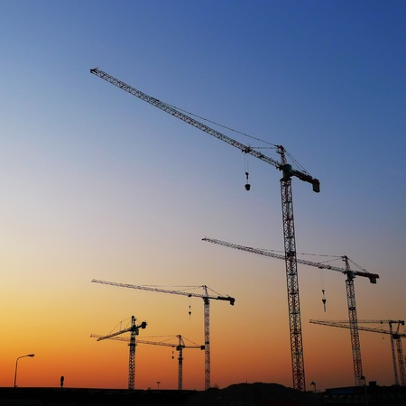 Construction site with silhouette of tower cranes on sunset, ready to start working. photo