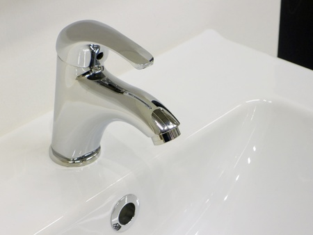 toilet sink: Elegant chrome faucet on clean and brilliant white sink. Stock Photo