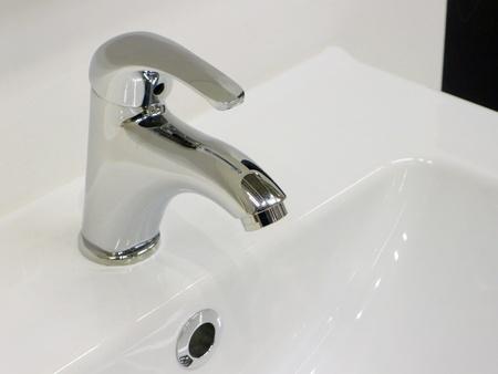 Elegante grifo cromado en el fregadero blanco limpio y brillante.