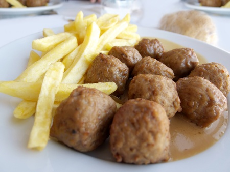 Closeup of Swedish meatballs with chips potatoes (French fries) and sauce. photo