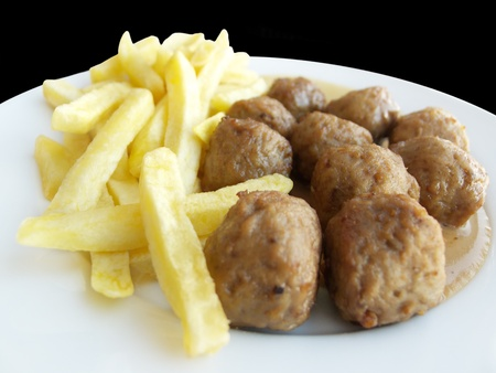 Closeup of Swedish meatballs with chips potatoes (French fries) and sauce. On black background. photo