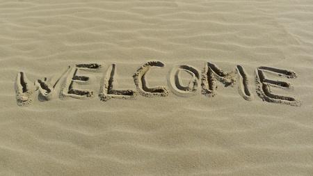 Bienvenido concepto con el cartel en la orilla del mar Foto de archivo