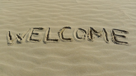 Welcome concept with sign on the sea shore  photo
