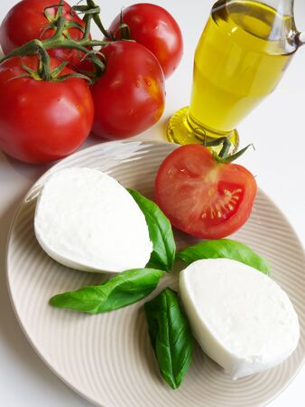 Genuine Italian tomatoes, mozzarella di bufala, olive oil and basil  Ingredients for mediterranean diet and caprese  photo