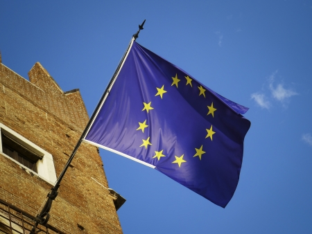 european economic community: European Union flag in a sunny day on blue and clean sky  Emblem of EU and Council of Europe