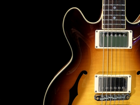 Close-up of vintage electric jazz guitar on black background