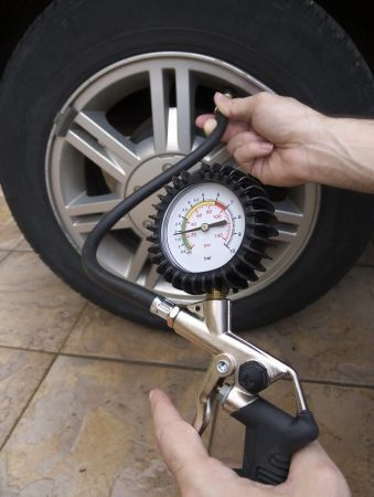 Close-up of manometer and man hands checking tire pressure with gauge  photo